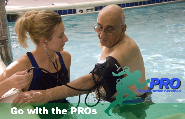 Physical Therapist with patient in pool.